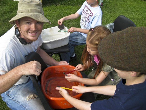 Darrell Rohl in community engagement action, teaching young children how to wash pots on site.